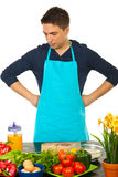 Confused man in kitchen. Confused man with blue apron standing in kitchen and looking on table with vegetables Stock Image