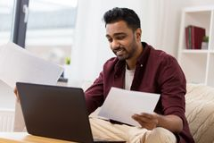 Confused man with laptop and papers at home Stock Photos