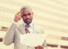 Confused man looking at documents outside corporate office building stock photography
