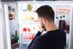 Confused Man Looking At Food In Refrigerator. Rear View Of A Confused Young Man Looking At Food In Refrigerator royalty free stock images