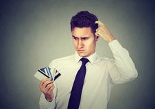 Confused man looking at many credit cards uncertain which one to choose. On gray background stock photo