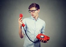 Confused teenager man looking at old fashioned telephone. Confused man looking at old fashioned telephone Stock Photo