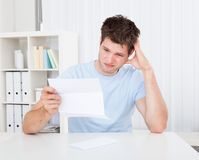Confused man looking at paper Stock Photo