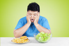 Confused man looking at salad and burger Royalty Free Stock Photo