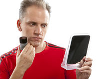 Confused man before a mirror the first time tries a man's against wrinkles cream Stock Photos