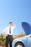 Confused man near a broken car thinking what to do Royalty Free Stock Photos