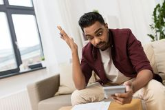 Confused man with papers and calculator at home. Business, accounting, finances and people concept - confused man with papers and calculator at home Royalty Free Stock Images
