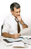 Confused Man Reading a Bill or Bank Statement. Businessman at desk in shirt and tie, reading a bill and looking worried and confused Stock Photos