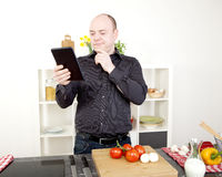 Confused man reading his tablet while cooking. Confused man reading his tablet with a pensive thoughtful look while standing in his kitchen, while cooking and Stock Image
