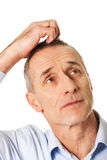 Confused man scratching his head Stock Image