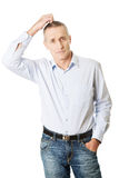 Confused man scratching his head Royalty Free Stock Images