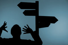 Confused man and signpost. Silhouette of confused man with hands in air under multiple directional signpost, light blue background Stock Image