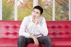 Confused man sitting on couch Royalty Free Stock Image