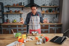 Confused man stand at table in kitchen. He look at colorful vegetables on desk. Man wear apron. Confused man stand at table in kitchen. He look at colorful royalty free stock images