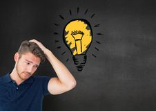 Confused man standing next to glowing light bulb icon Royalty Free Stock Photography