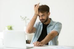 Confused man stressed about performing mistake in report. Confused irritated funny young man stressed about performing mistake while preparing annual financial Stock Images