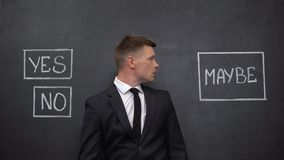 Confused man in suit doubting between yes, no and maybe buttons on blackboard
