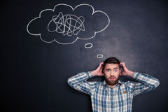Confused man thinking about problem with black board behind him. Confused bearded young man grabbing his head and thinking about problem with black board behind Royalty Free Stock Image