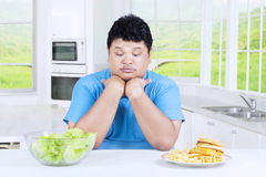 Confused man to choose salad or burger. Portrait of confused overweight person to choose salad or burger, sitting in the kitchen at home Stock Photography
