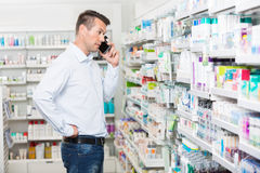 Confused Man Using Mobile Phone In Pharmacy Royalty Free Stock Photography