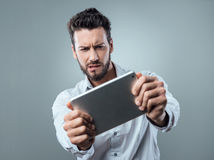 Confused man watching his tablet Stock Image