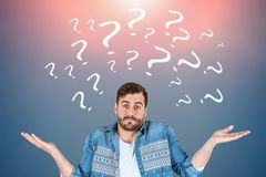 Confused man, white question marks. Man in casual clothes shrugging shoulders in gray room with question marks drawn on the wall. Concept of doubt. Toned image stock photography