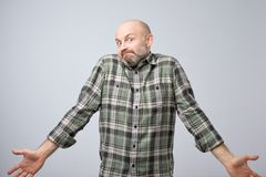 Confused mature bearded man standing and shrugging shoulders isolated over white background. I do not know the solution of this problem concept royalty free stock image