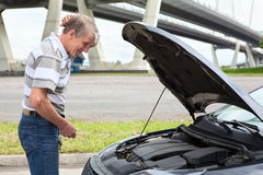 Confused mature driver standing in front of vehicle with opened engine Royalty Free Stock Image