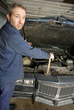 Confused mechanic. A bewildered mechanic unsure of what is wrong with the old car royalty free stock images
