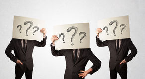 Confused men in formal gesturing with question marks on cardboar Royalty Free Stock Images