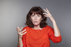 Confused middle aged lady with red jumper Royalty Free Stock Images