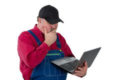 Confused middle-class worker standing thinking. As he peers at a handheld laptop computer unsure of what he is reading isolated on white royalty free stock images