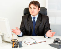 Confused modern business man sitting at desk Royalty Free Stock Photos