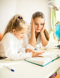 Confused mother looking at daughters homework Stock Photos