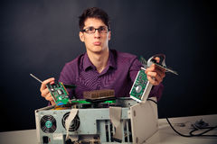 Confused Nerd With Lots Of Hardware. Confused nerd with lots of computer hardware royalty free stock photos