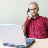 Confused office worker. On the phone working at the desk with laptop royalty free stock images