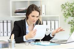Confused office worker reading documents. On a desktop Royalty Free Stock Image