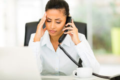 Confused office worker. Talking on telephone in office Royalty Free Stock Image