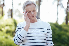 Confused old man feeling awful pain in his head outdoors Royalty Free Stock Photography