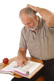 Confused older student. At a desk reading a book Royalty Free Stock Photo