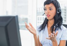 Confused operator looking at her computer Royalty Free Stock Images