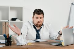 Confused overweight businessman sitting at workspace with documents. And laptop Royalty Free Stock Image