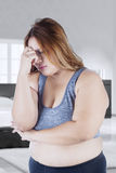 Confused overweight woman in bedroom. Overweight woman standing in the bedroom and looks confused while thinking something Stock Photo