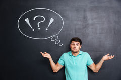 Confused perplexed young man shrugging shoulders over chalkboard background. With blank speech bubble Royalty Free Stock Image