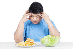 Confused person choosing hamburger or salad. Photo of a stressful person having choice between hamburger and salad, isolated on white background stock photo