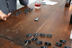 A confused person plays dominoes on a brown wooden table. Dominos on a table with a girl confused as to how to play Royalty Free Stock Photography