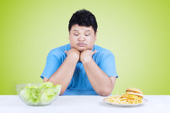 Confused person to choose a food. Overweight person looks confused to choose salad or hamburger on the table Stock Photography