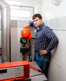 Confused plumber looking at complicated heating system Stock Image