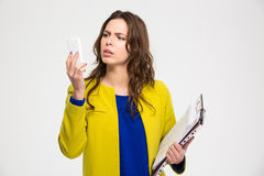 Confused pretty young woman holding folders and using smartphone Stock Photo