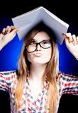 Confused and puzzled young girl holding exercise book on her head Royalty Free Stock Photo